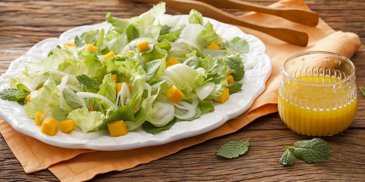 Fotografia em tons de marrom em uma bancada de madeira com um pano laranja e um prato branco oval com as hortaliças. Ao lado, um pegador de salada de madeira e um copo de vidro com suco de laranja.