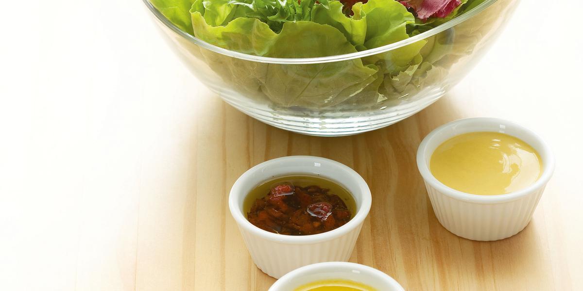 Fotografia em tons de verde em uma mesa de madeira clara com um bowl de vidro com salada de alface e rúcula e ao lado, quatro potinhos brancos com os molhos de morango, mostarda, hortelã e gengibre.