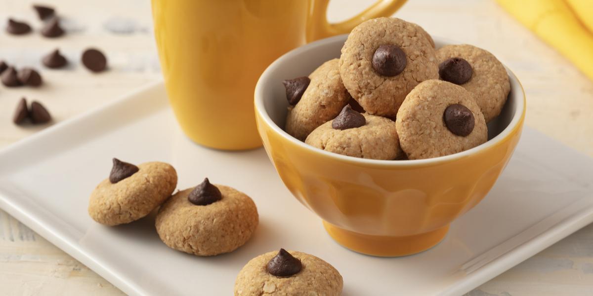 Fotografía en tonos de blanco y amarillo de una encimera blanca con un plato cuadrado, encima una taza amarilla, un recipiente amarillo redondo con galletas y tres galletas. Al fondo un paño amarillo y gotas de chocolate.