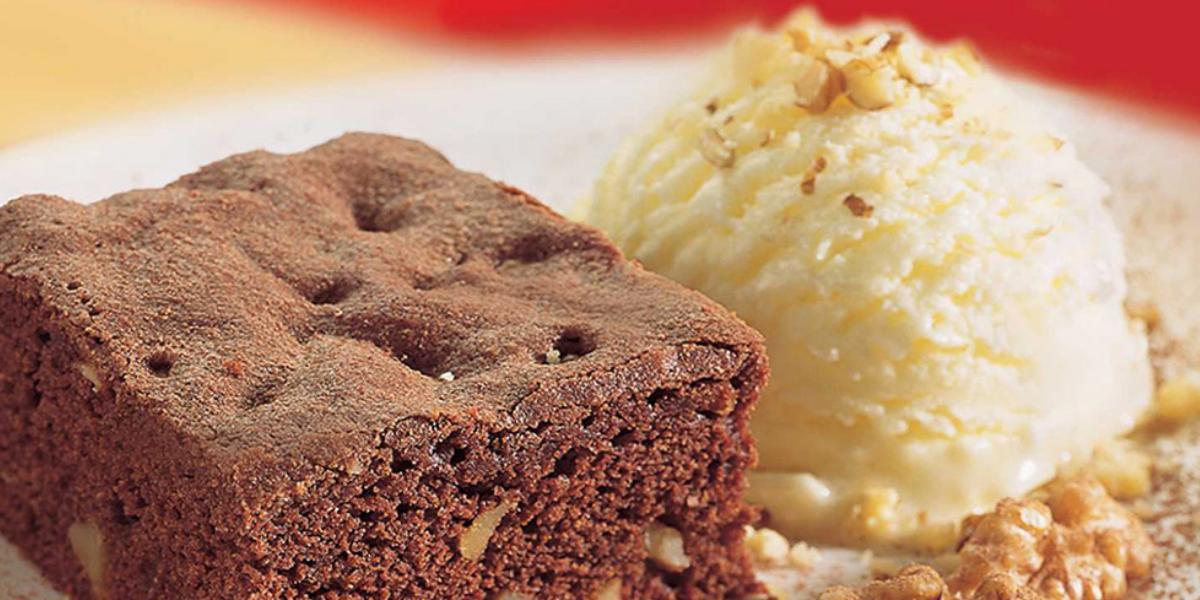 Fotografia em tons de marrom em uma bancada de madeira com uma foto aproximada de um prato polvilhado com cacau em pó, um brownie de chocolate e sorvete de creme.
