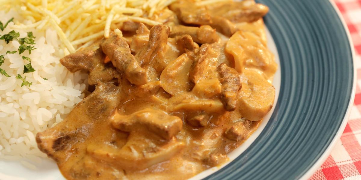 Foto tirada de cima de um prato azul com strogonoff de carne dentro, arroz e batata palha