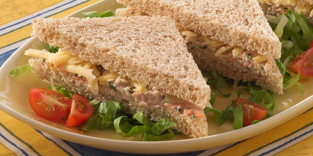 Fotografia em tons de amarelo e azul, um recipiente branco contém dois sanduíches com folhas e fatias de tomate em volta