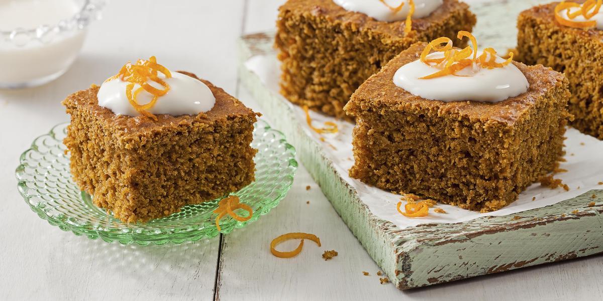 Fotografia em tons de branco e marrom de uma bancada branca vista de cima, um prato cor verde contém um pedaço quadrado de bolo e uma tabua de madeira contém outros 3 pedaços de bolo no formato quadrado