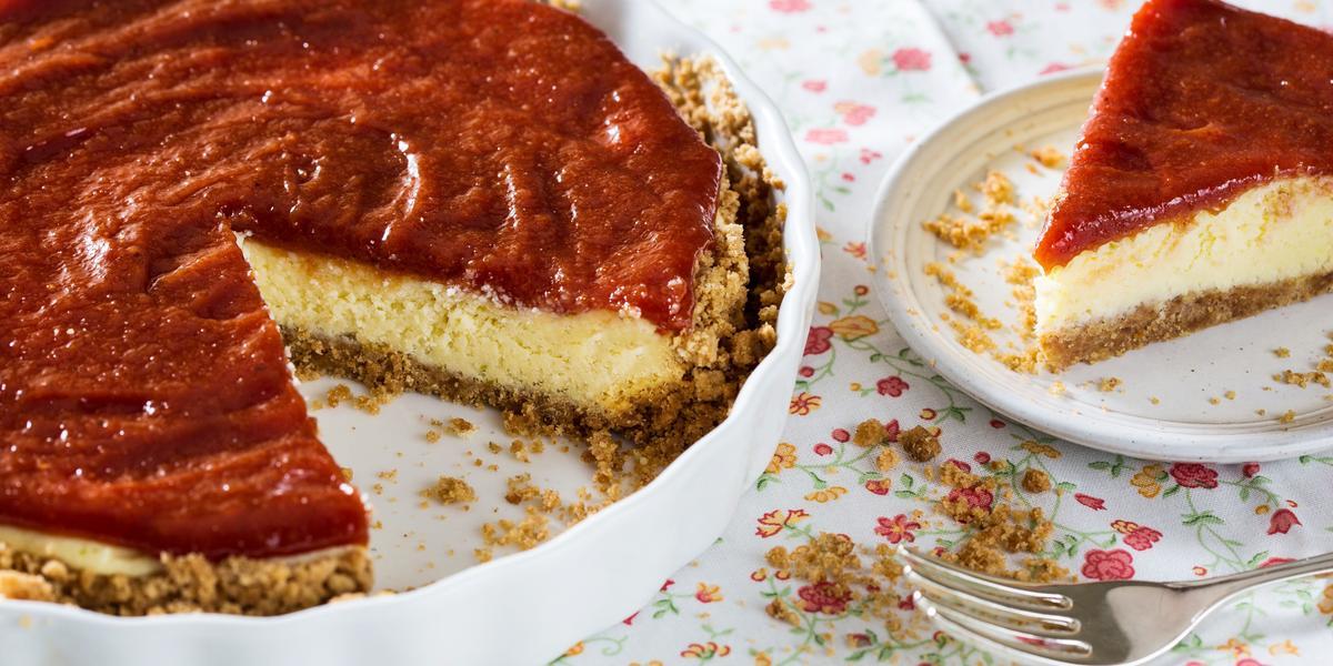 Fotografia em tons de vermelho em uma mesa com uma toalha branca com flores coloridas, um recipiente redondo raso com a cheesecake dentro dele. Ao lado, um prato raso branco com uma fatia da cheesecake.