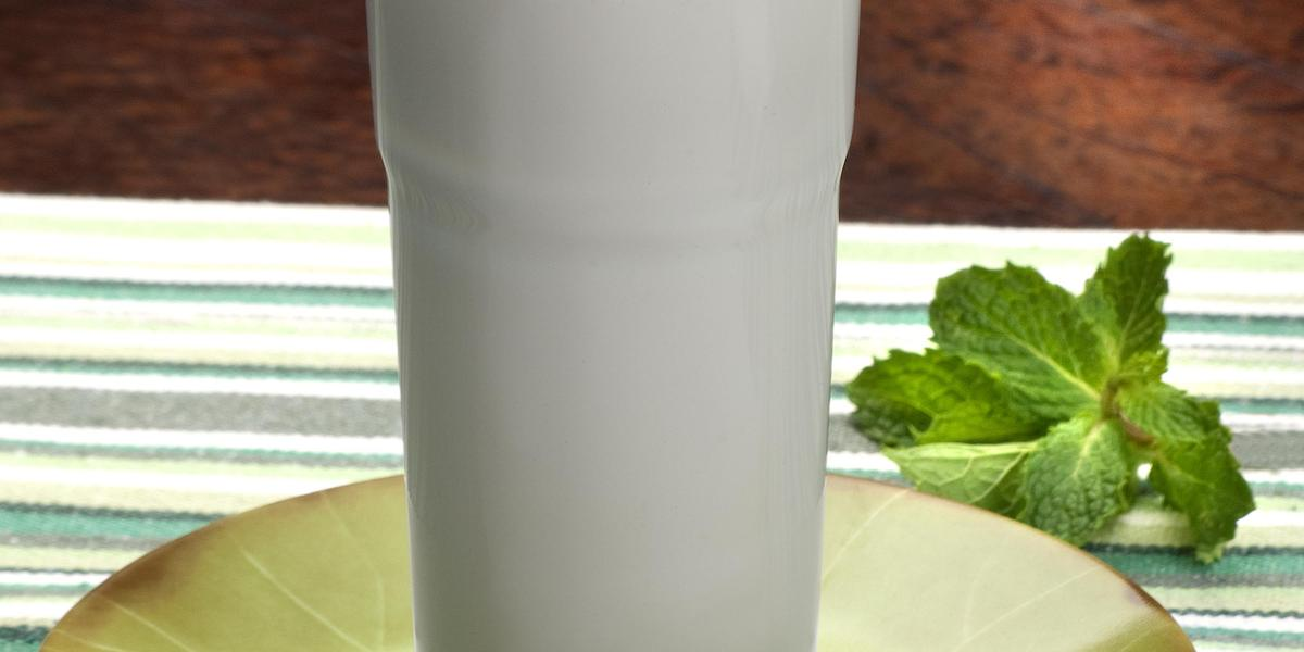 Fotografia em tons de branco, azul e verde, tendo ao centro copo com bebida em tom de branco sobre pires verde, ao lado ramo de hortelã, tudo sobre toalha listrada em branco, verde e cinza, sobre bancada em tom terroso.