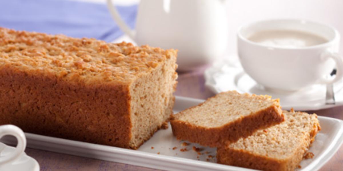 Fotografia em tons de branco em uma bancada de madeira clara com um prato retangular branco com o pão integral sobre ele e duas fatias já cortadas. Ao fundo, uma xícara branca e um bule branco pequeno.