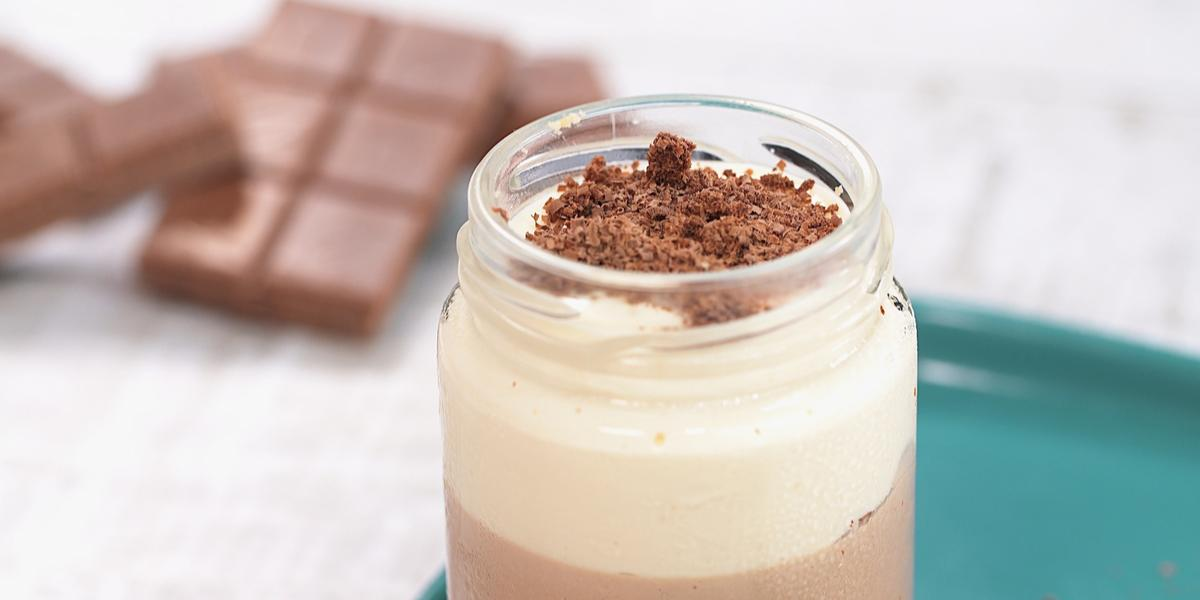 Fotografia em tons de branco e azul de uma bancada branca com um prato retangular azul, sobre ele um copo de vidro com o cheesecake. Ao fundo tabletes de chocolate.