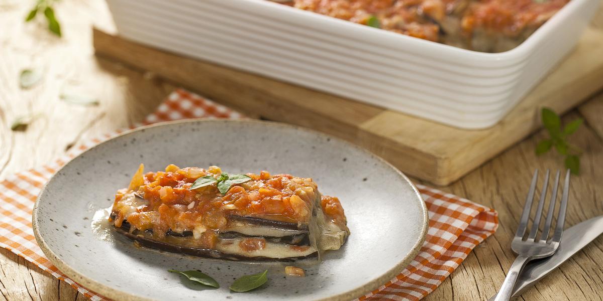 Fotografia em tons de branco e vermelho, ao centro está um prato com uma fatia da lasanha de berinjela em cima de um guardanapo laranja quadriculado e ao fundo está um refratário com o restante da lasanha. A direita estão um garfo e uma faca.