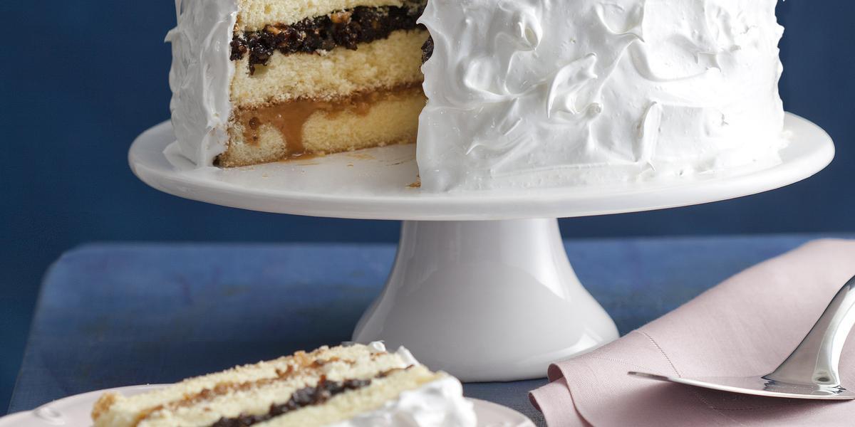 Fotografia em tons de branco e azul, ao fundo, sobre bancada azul, uma boleira de porcelana com bolo fatiado coberto com marshmallow e recheio de ameixa, prato de sobremesa com bolo de ameixa, dois pratos com talheres e um guardanapo com uma espátula.