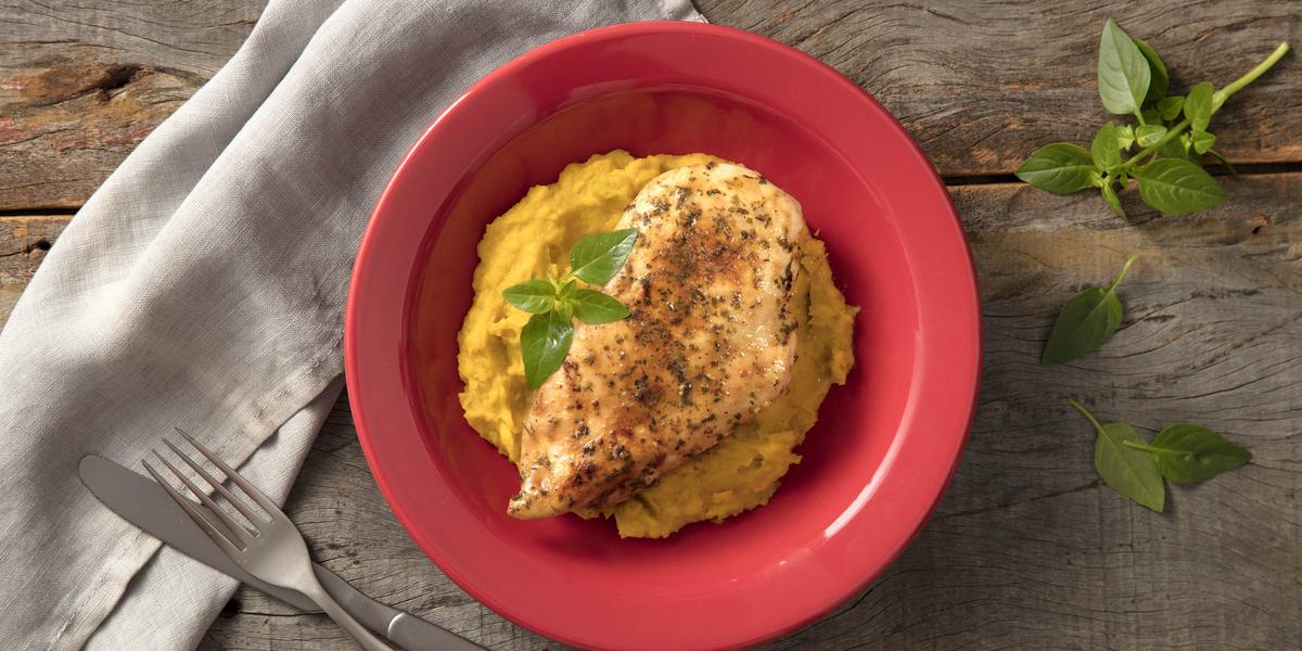 Fotografia em tons de vermelho em uma bancada de madeira com um pano cinza, um prato vermelho fundo com o purê de abóbora e filé de frango em cima e dentro do prato. Ao lado, garfo e faca.
