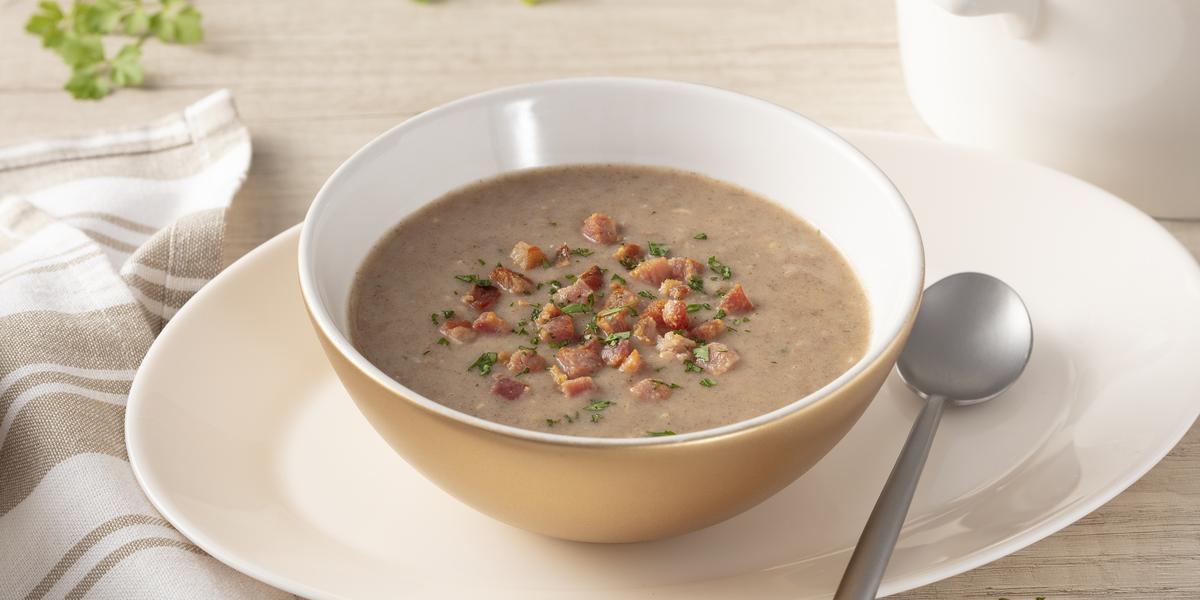 Fotografia em tons de bege de uma bancada com um prato oval, sobre ele um bowl bege com a sopa de feijão e pedacinhos de bacon. Ao lado uma colher prateada. Ao redor um pano listrado branco e bege, ramo de salsinha e um pote branco.