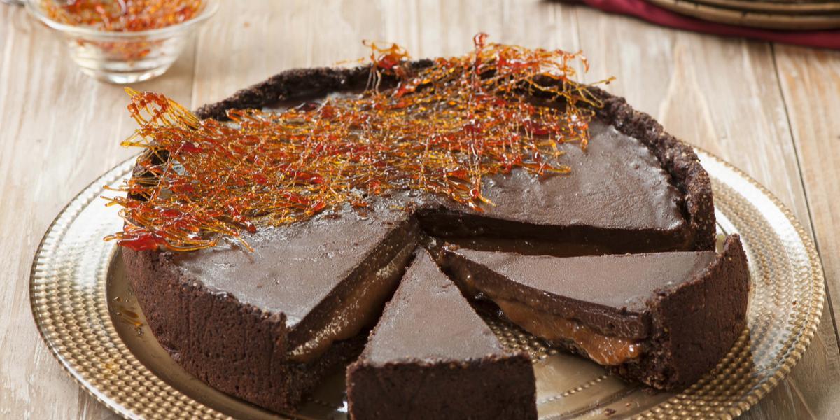 Fotografia em tons de marrom e chocolate, mostrando bancada em tons de marrom e branco contendo prato dourado com uma torta de chocolate decorada com fios de caramelo, ao fundo pratos e garfos, potinho com calda de caramelo e potinho com fios de caramelo.