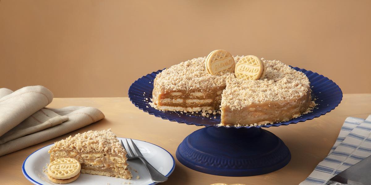 Foto de uma mesa marrom clara, com uma boleira azul escura. Sobre ela está a receita da Torta de Palha Italiana decorada com Biscoitos Bono Doce de Leite. Na mesa há um prato com uma fatia, mais alguns biscoitos Bono e guardanapos de tecido.