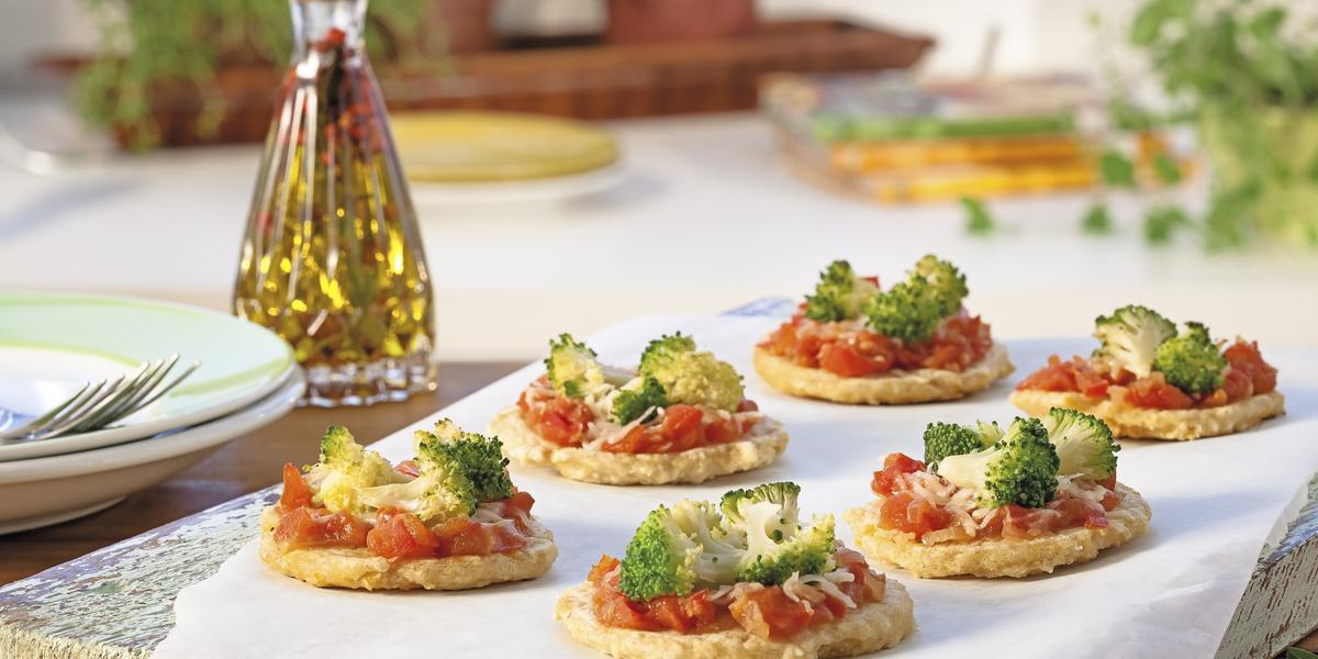 Fotografia em tons de amarelo e verde em uma bancada de madeira, com uma mesa arrumada para um jantar. Ao centro, uma tábua de madeira com um papel manteiga e várias mini pizzas com tomate e brócolis em cima dele.