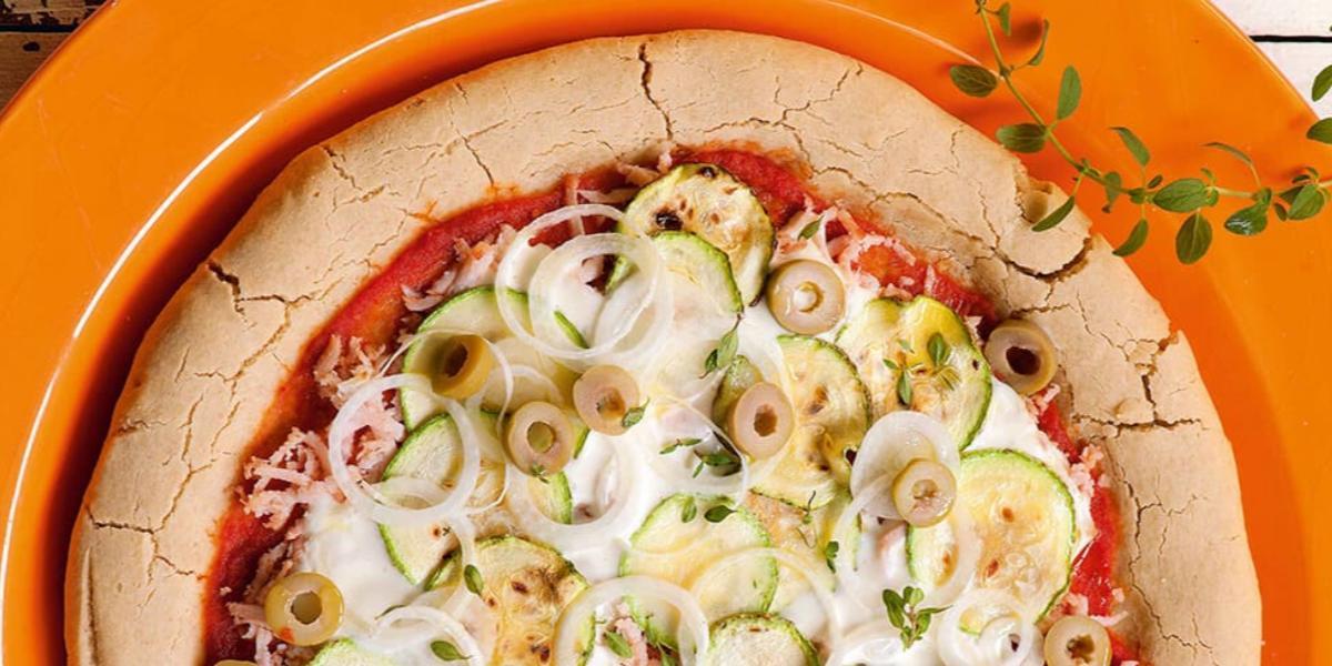 em um prato redondo laranja contém uma pizza com abobrinha, peito de peru e requeijão.