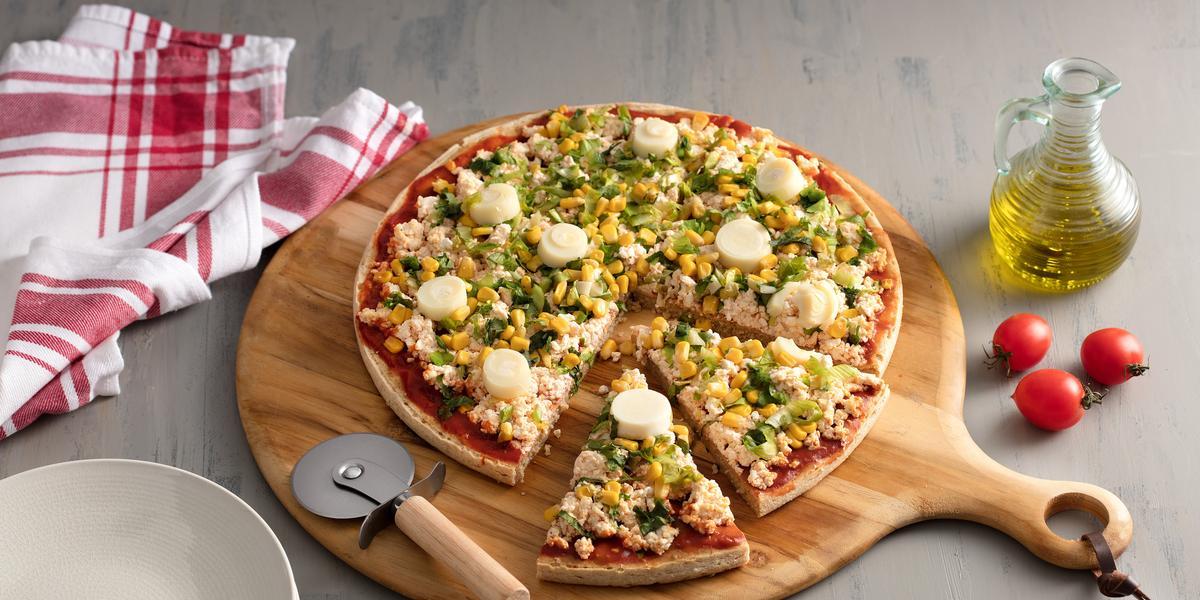 Fotografia em tons de vermelho em uma bancada de madeira cinza com uma tábua de pizza de madeira com a pizza em cima decorada com escarola e ricota. Ao lado, um vidro de azeite, tomates e um cortador de pizza.