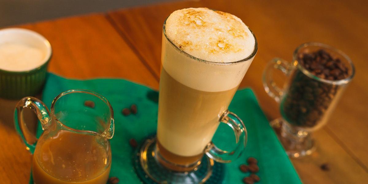 Fotografia em tons de verde de uma mesa de madeira com um paninho verde, uma xícara com a bebida e grãos de café decorando.