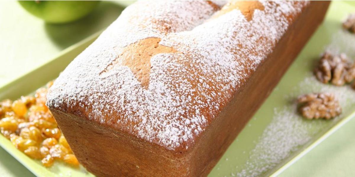 foto em tons de verde e marrom tirada de um recipiente verde e por cima um bolo inglês com açúcar polvilhado por cima