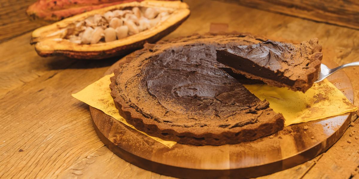 Fotografia em tons de marrom de uma bancada de madeira com uma tábua de madeira, sobre ela um paninho amarelo com uma torta de chocolate e uma espátula retirando uma fatia. Ao fundo um cacau.