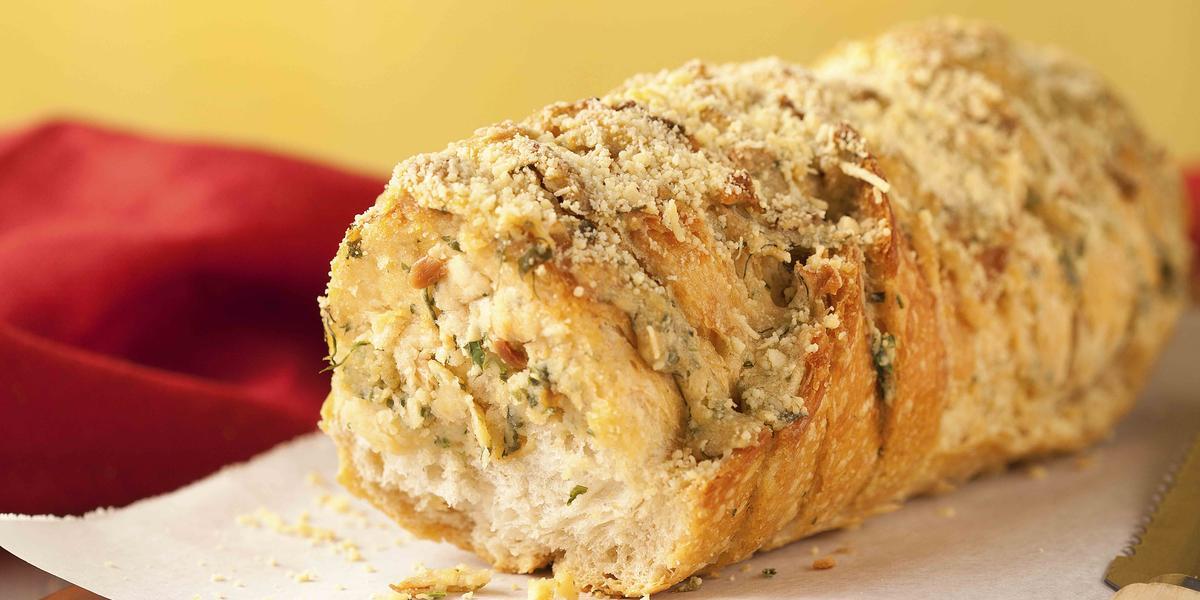 Fotografia em tons amarelo e vermelho em uma bancada de madeira clara, uma tábua de madeira com um papel toalha e o pão de cebola em cima dele. Ao lado, uma faca de pão e uma fatia do pão em cima de um pratinho branco pequeno.