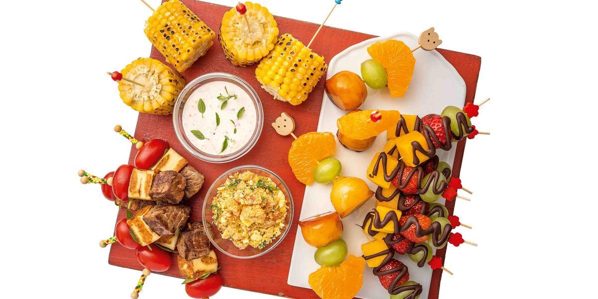 Fotografia em tons de laranja em uma bancada branca com uma toalha vermelha, um recipiente com vários espetinhos de legumes, potinhos com molhos e também espetinhos de fruas com chocolate.