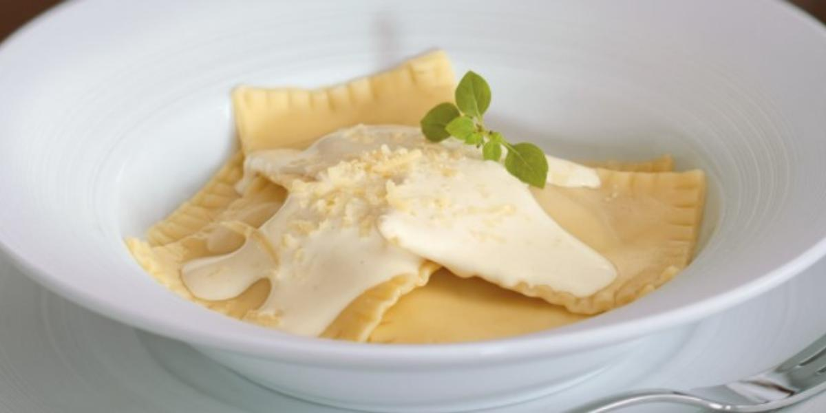 Fotografia em tons de amarelo em um fundo branco com um prato redondo grande, largo e branco com ravioli de abóbora com gorgonzola e molho branco em cima.