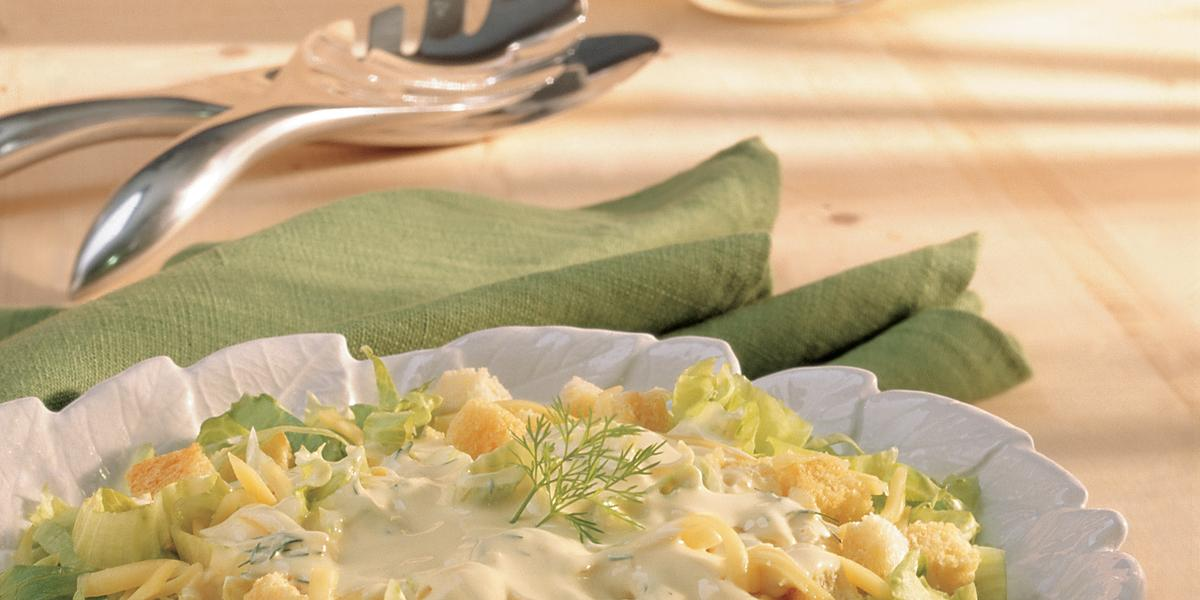 Fotografia em tons de verde em uma bancada de madeira clara, um pano verde, um pegador de salada e um prato redondo branco fundo com a salada de alface, queijo, torradinhas e iogurte dentro.