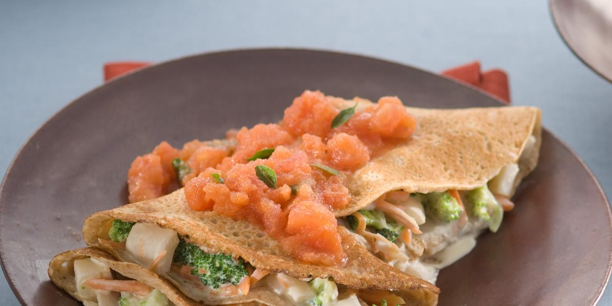 Fotografia de um prato marrom com 2 panquecas feitas em forma de crepe e recheadas com legumes e cobertas com molho de tomate, sobre guardanapo vermelho e toalha azul clara.