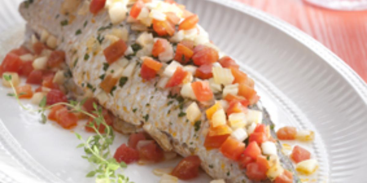 Fotografia em tons de vermelho e branco de uma bancada vermelha, sobre ela um prato branco com o peixe  e um garfo. Ao fundo taças de água.