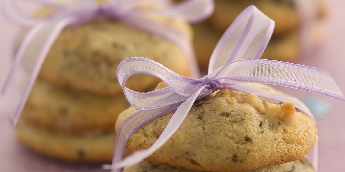Foto com 3 cookies um em cima do outro amarrados com um cetim rosa, no fundo da foto há outros 2 cookies da mesma maneira