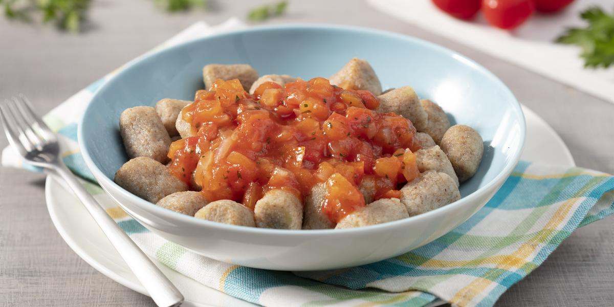 Fotografia em tons de azul com fundo cinza com um prato raso branco, paninho xadrez azul e amarelo, garfo, um prato fundo azul com nhoque e molho de tomate.