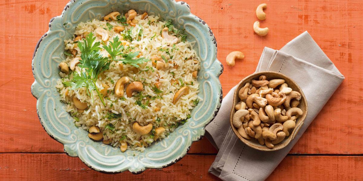 em uma mesa na cor vermelha, contém dois recipientes. Um contém o arroz e o outro as castanhas-de-caju.