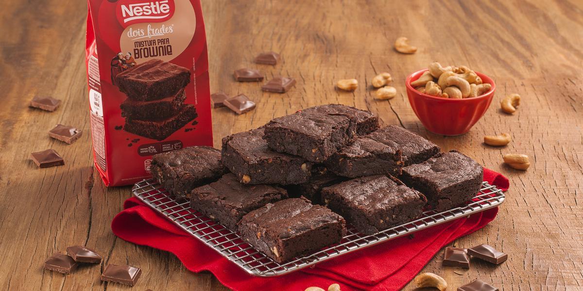 Fotografia em tons de marrom e vermelho de uma bancada de madeira com um paninho vermelho, sobre ele um prato retangular com pedaços de brownie. Ao fundo um pacote de brownie dois frade e um recipiente redondo com castanha-de-caju.