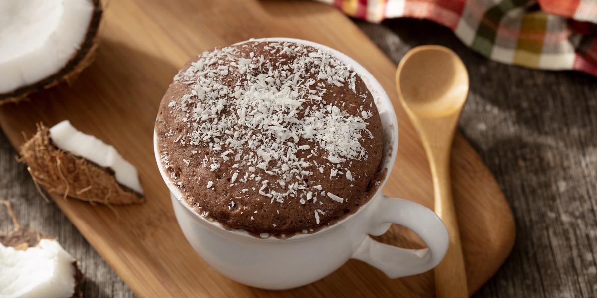 fotografia em tons de marrom e branco de uma bancada marrom vista de cima, contém uma tábua de madeira com uma xicara branca com bolo de prestígio e coco ralado por cima para decorar