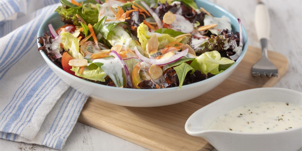 Fotografia em tons de branco e azul de uma bancada branca e uma tábua de madeira, sobre ela um recipiente redondo com a salada e um garfo. Ao lado uma molheira branca com o molho e um paninho branco e azul.