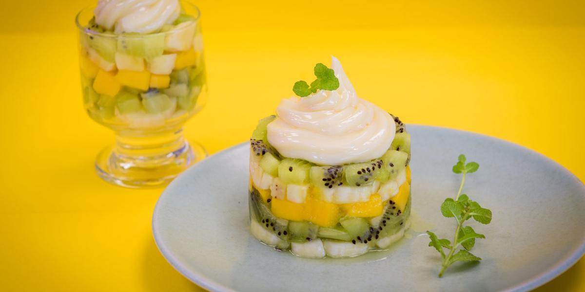 fotografia em tons de amarelo e branco, contém um prato redondo e branco com Tartar com pedaços de frutas e creme por cima e ao fundo uma taça transparente com pedaços de frutas e creme por cima.