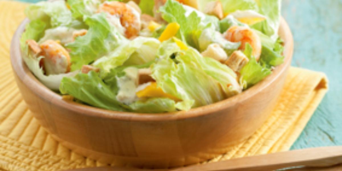 Fotografia em tons de azul, amarelo e marrom de uma bancada azul com um paninho amarelo, sobre ele um bowl de madeira com salada e uma colher e um garfo de madeira. Ao fundo pratos redondos brancos.