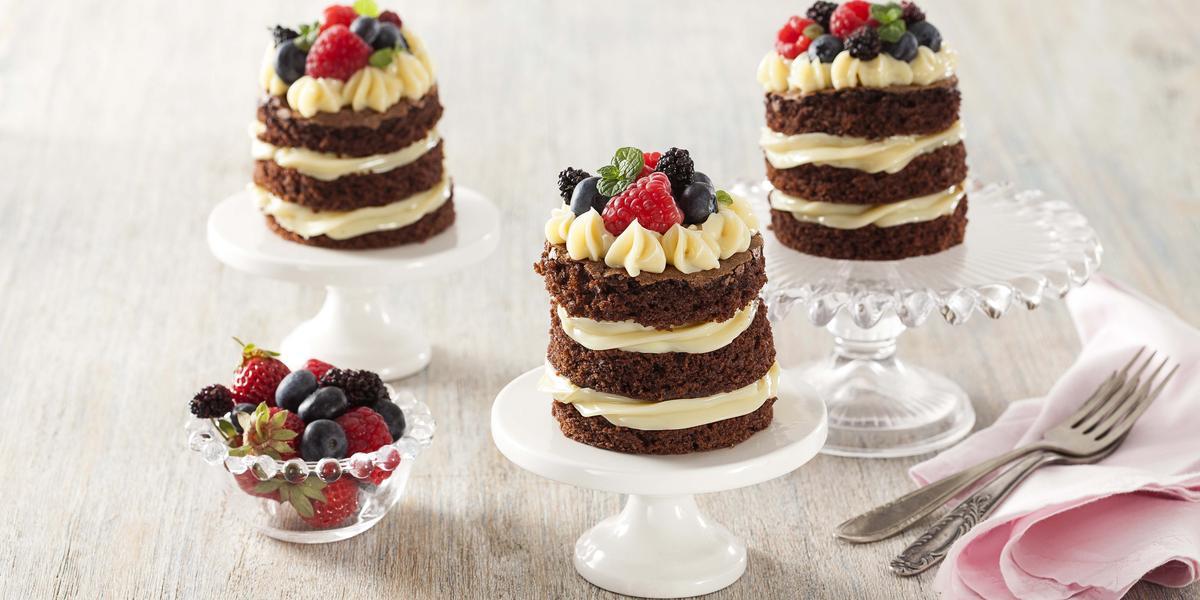 Fotografia em tons de branco e cinza de uma bancada cinza com com suportes de bolos brancos e de vidro com naked cakes. Ao lado um paninho rosa com garfos e um recipiente redondo de vidro com frutas vermelhas.