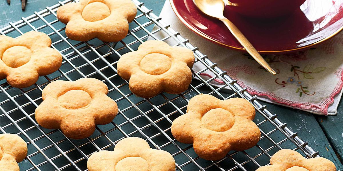 Fotografia em tons de azul de uma bancada azul, sobre ele uma grade prata com biscoitos de gengibre em forma de flor. Ao lado uma xícara de café vermelha com uma colher.