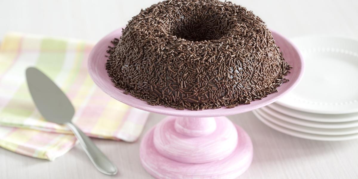 Foto de um brigadeirão de chocolate em cima de um prato de bolo rosa e com pratos brancos atrás