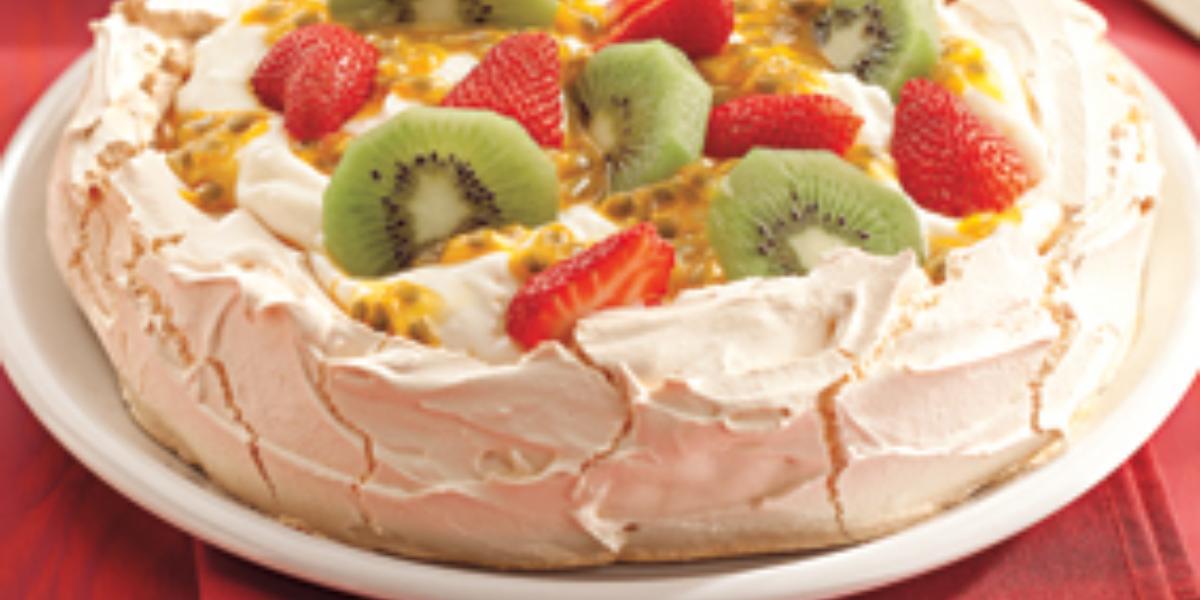 Fotografia em tons de vermelho de uma bancada com um pano vermelho sobre ele um prato branco com Pavlova. Ao fundo uma colher.