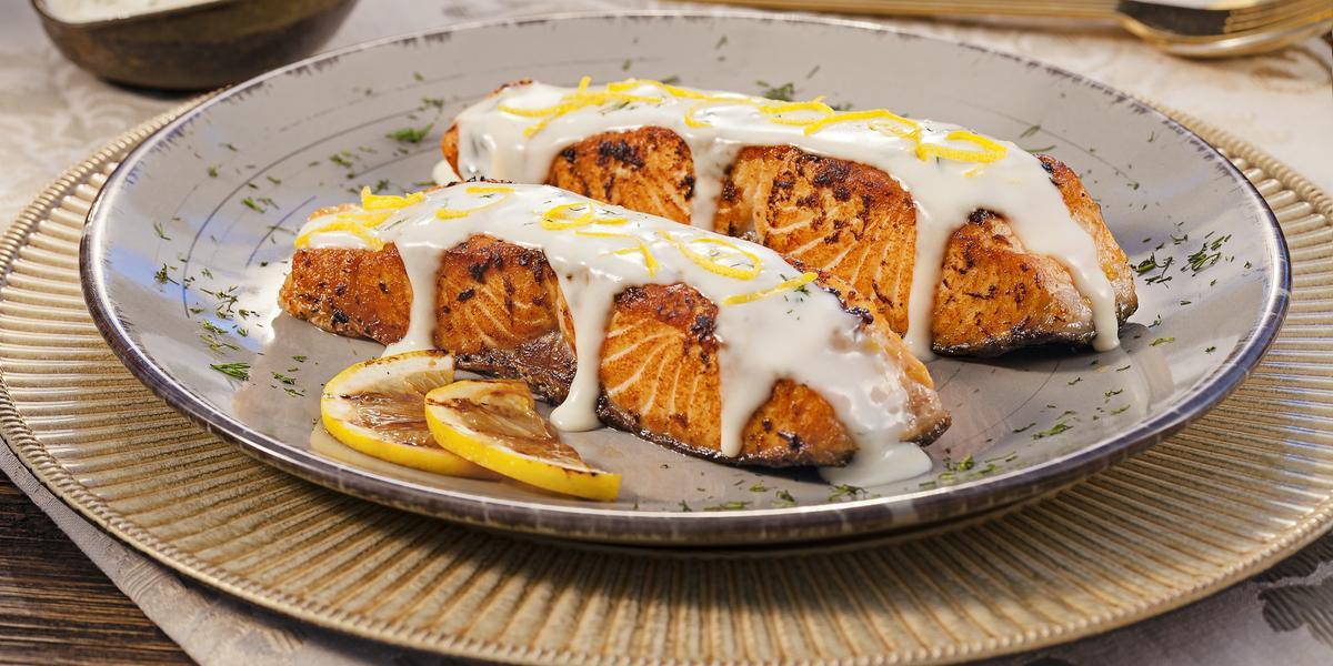 Fotografia em tons de laranja em uma bancada de madeira, uma toalha branca de renda, um sousplat dourado, um prato redondo com detalhes em azul e duas postas de salmão com molho de limão em cima dele.