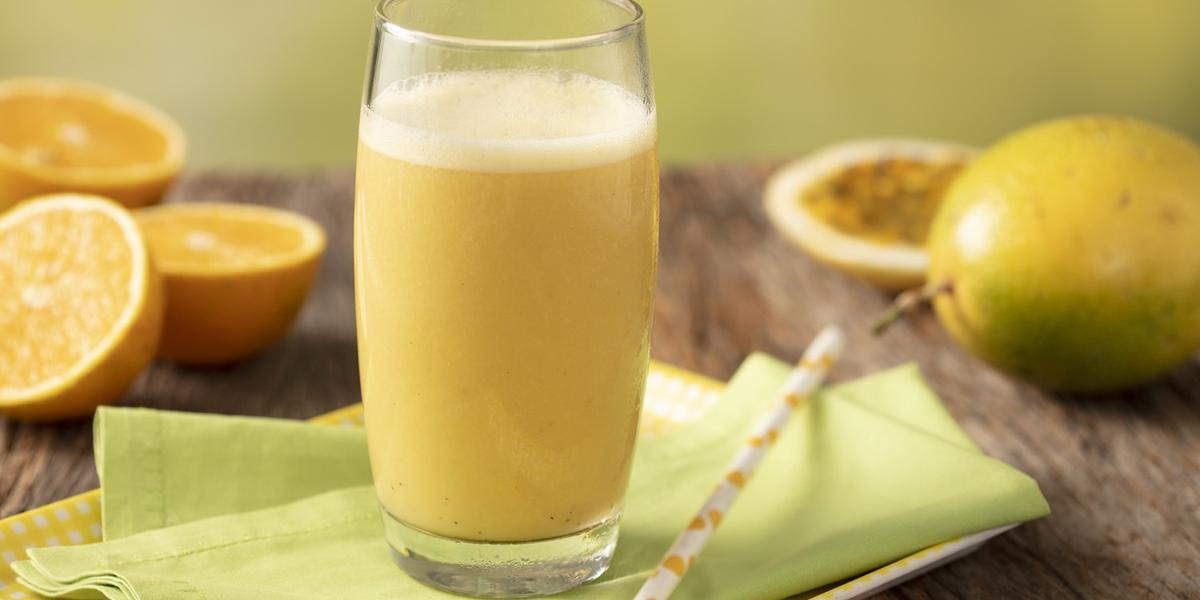 Fotografia em tons de amarelo, verde e marrom de uma bancada de madeira com uma bandeja amarela e um paninho verde com um canudo sobre ele um copo de vidro com a vitamina de laranja. Ao fundo três metades de laranjas, um maracujá inteiro e uma metade.