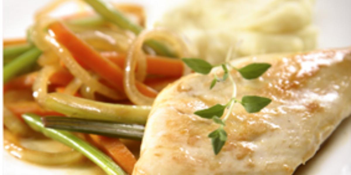 Em um prato quadrado e branco contém um pedaço de frango servido com cenoura, cebola e salsão.