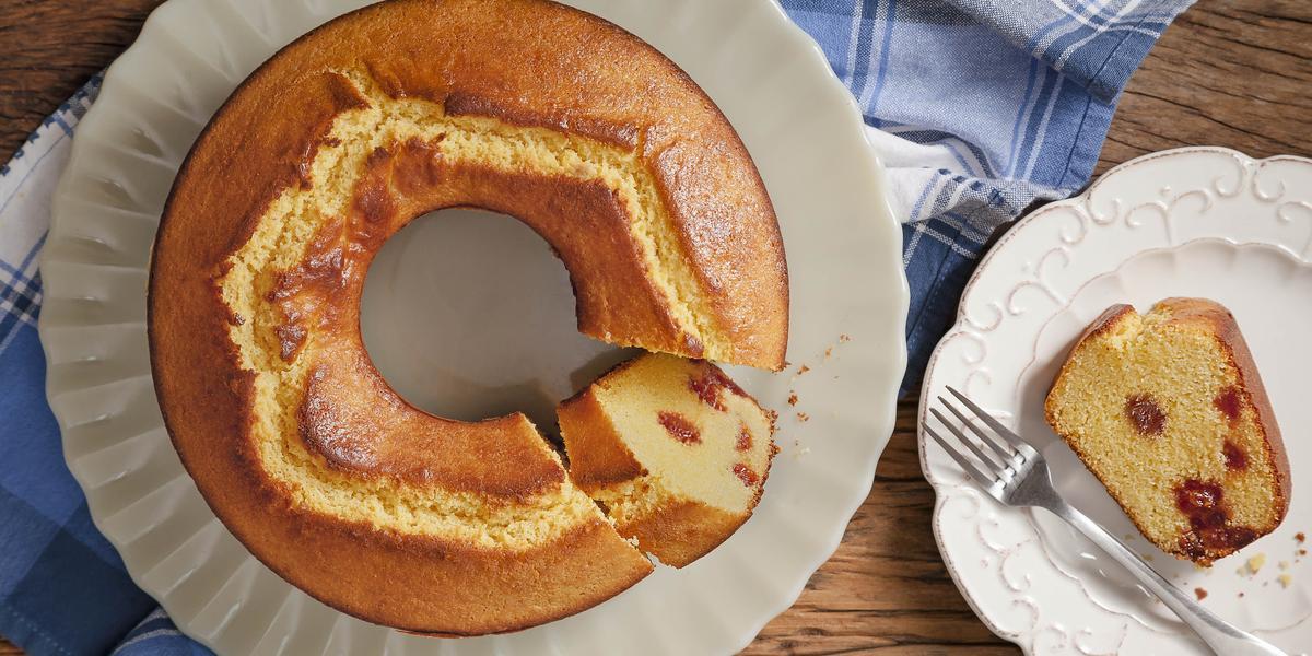 Fotografia em tons de marrom e azul de uma bancada vista de cima, ao centro um pano na cor azul, uma travessa branca com o bolo e um prato branco ao lado com uma fatia de bolo e um garfo.