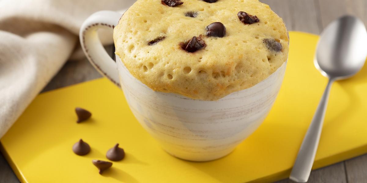 Fotografía en tonos marrones. blanco y amarillo de un banco de madera con un tablero amarillo, sobre él una taza blanca con pastel de taza y una cuchara. Al fondo una tela blanca.