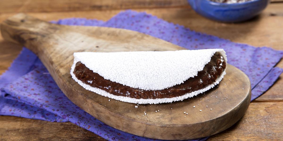 Fotografia em tons de marrom e roxo de uma bancada de madeira com um paninho roxo, sobre ele um tábua de madeira com uma tapioca. Ao fundo um recipiente roxo com creme de dark chocolate.