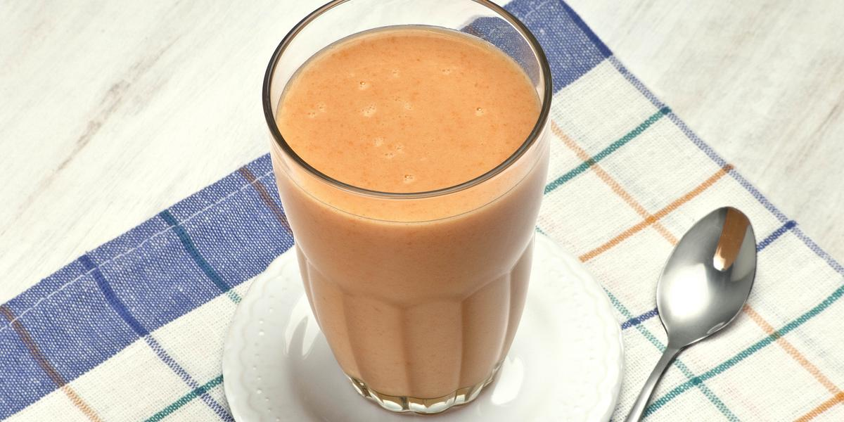 acima de um pano listrado nas cores azul e branco, contém um pratinho com o copo da vitamina e ao lado uma colher.
