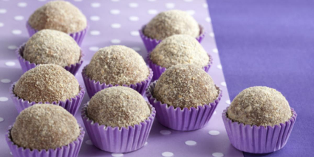 Fotografia em tons de roxo em uma mesa com uma toalha roxa escura, um paninho lilás com bolinhas brancas e vários brigadeiros de cookie dentro de forminhas de docinhos roxa.