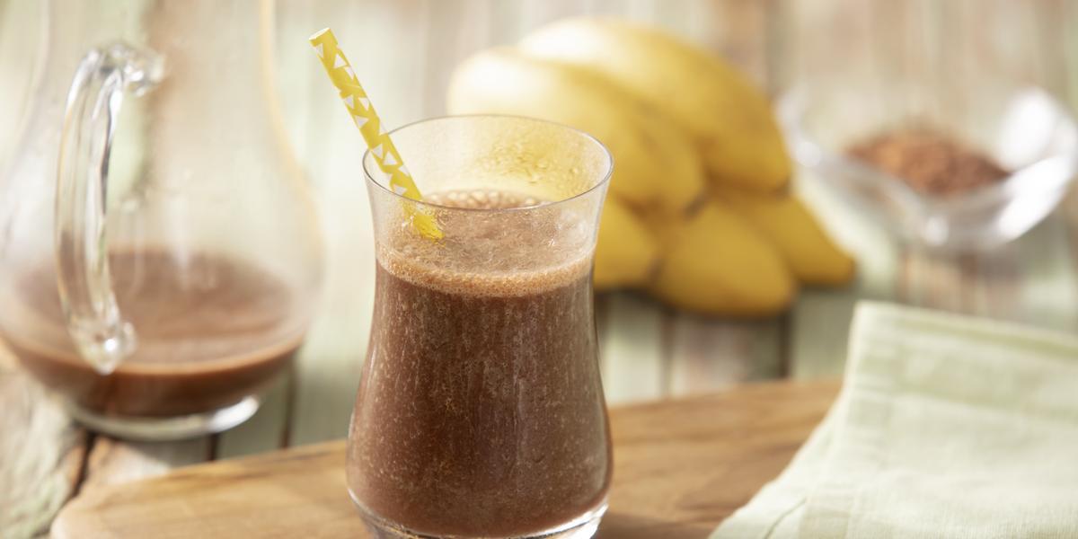 Fotografia em tons de marrom e amarelo de uma bancada de madeira com uma tábua, um paninho verde e um copo com a bebida dentro e um canudo de papel amarelo. Ao fundo uma jarra com a bebida, bananas e cacau.